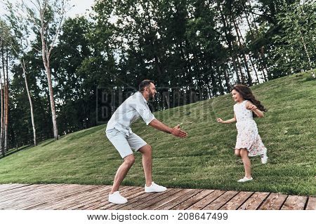 Sincere joy. Young loving father keeping arms outstretched while his smiling daughter running to him outdoors