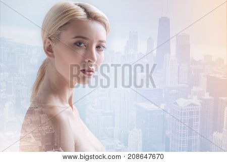 Beautiful appearance. Adorable young model having serious expression on her face while standing against urban background