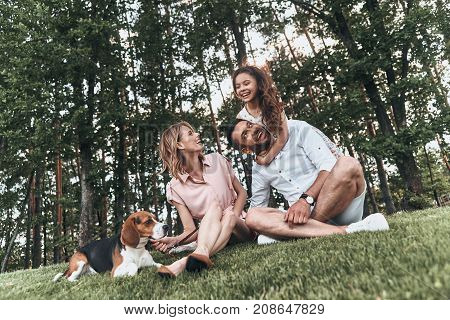 Family bonding time. Happy young family of three with dog smiling while sitting on grass in park