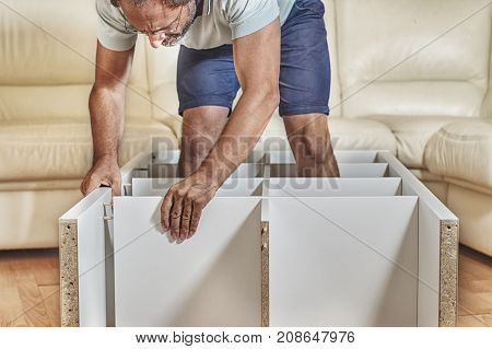 Middle-aged man assembling a shelving at home