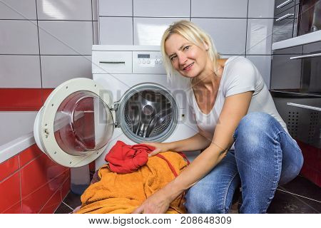 The housewife is kneeling at a pile of dirty laundry. Open washer is in the background. All potential trademarks are removed.