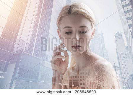 Magnetic appearance. Close up of charming girl looking down while standing against city view