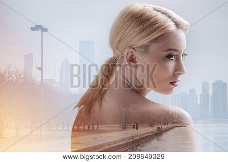 Delightful day. Close up of adorable girl turning around while standing in urban surrounding