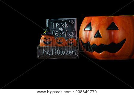 Halloween concept : Low key image of ceramic pumpkins Halloween and trick or treat sign and ceramic Halloween Pumpkin bucket isolated on black background