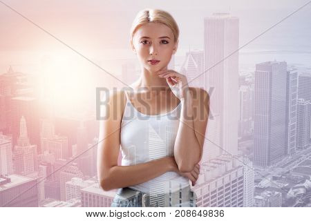 Charming look. Waist up of young lovely model standing in front of you while touching her face with a finger and being thoughtful