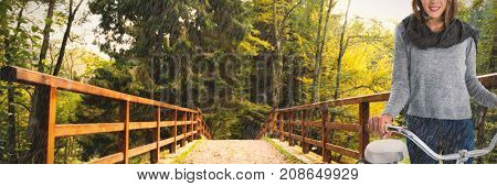 Portrait of woman standing by bicycle against bridge with railings leading towards forest