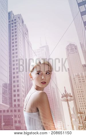 Having a walk. Pleasant charismatic girl looking away and being calm while standing against city buildings