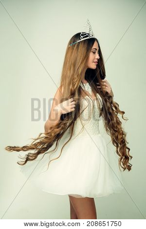 Hairdresser and cosmetics. Beauty salon and wedding fashion. Woman with long hair white dress and crown. Haircare and prom queen. Girl has fashionable makeup and healthy hair on grey background.