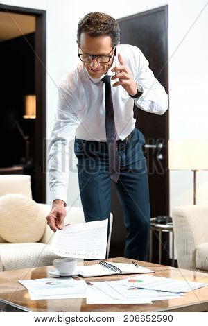 Businessman Reading Paperwork And Talking On Phone