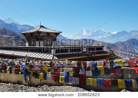 The Buddhist monastery is high in the mountains with a large number of flags near Muktinath