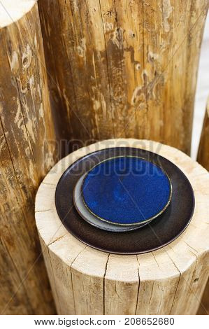 Vintage blue and black plates on a wooden stump