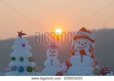 Snowmen With Smiley Faces In Hats On Evening Landscape