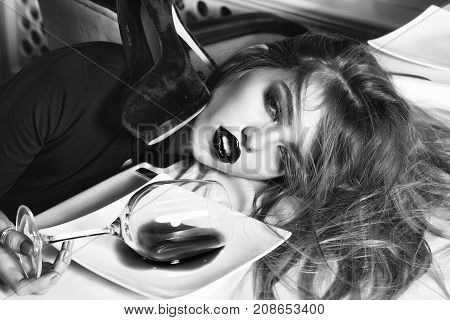 Sensual elegant glamour young drunk woman with beautiful hair lying on table with glass and poored red wine in plate after hangover with suide shoe horizontal picture