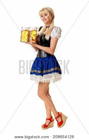 Full length portrait of a blond woman with traditional costume Dirndl holding beer glasses isolated on white background. Oktoberfest