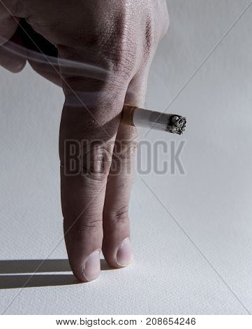 close up man hand with burning cigarette as penis in smoking cause sexual erectile dysfuntion and impotence warning concept isolated on clear background
