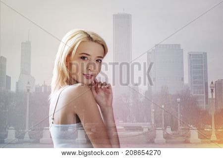 Optimistic mood. Close up of pretty model touching her face with a finger while standing in front of you and smiling