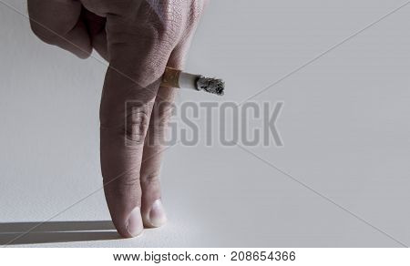 close up man hand with burning cigarette as penis in smoking cause sexual erectile dysfunction and impotence warning concept isolated on clear background