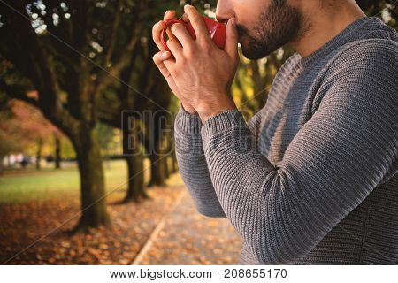 Side view of thoughtful man having coffee against footpath amidst trees at park