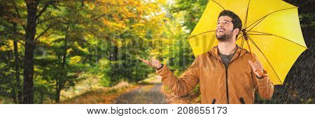 Full length of young man holding yellow umbrella against scenic shot of narrow road along forest