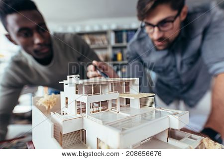 Close up shot of scale model house on table with architects. Two architects making architectural model in office together.
