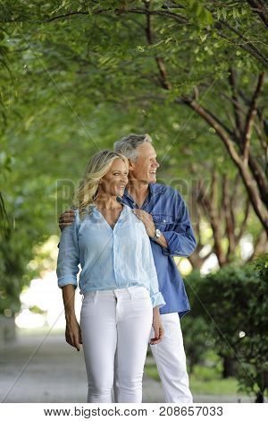Mature Couple Posing Under Arching Trees