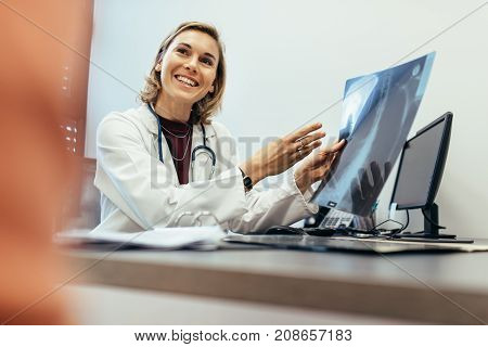 Smiling medicine professional explaining diagnosis of x-ray to patient in clinic. Female physician explaining medical scan result to her patient.