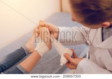Be attentive. Close up of kids leg that being in male hand, competent doctor bandaging foot