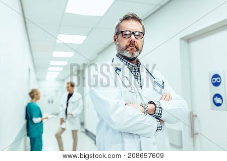 Portrait of experienced doctor standing in hospital corridor with his arms crossed. Caucasian mature physician with colleagues standing in background.
