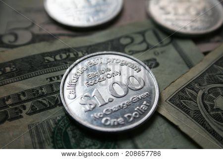 Welfare EBT Coin On Top Of $20, $5 & $1 Dollar Bill