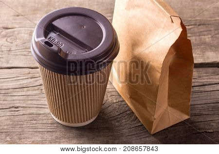 Tea and snacks for breakfast. A cup of tea or coffee and a paper bag with a snack on a wooden table