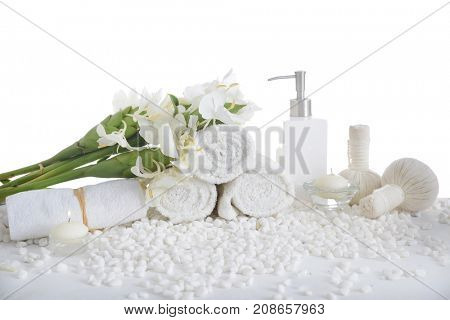 Tropical ginger flower on three rolled towel ,bottle oil with herbal ball on pile of white stones