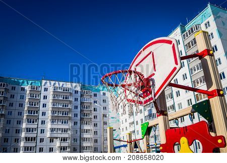 a basketball ring on the playground stands in the courtyard of residential buildings with windows and balconies under a blue sky with no clouds