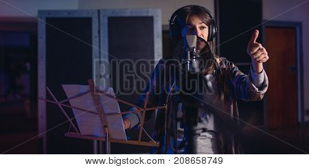 Female Singer With Thumbs Up Sign In Recording Studio