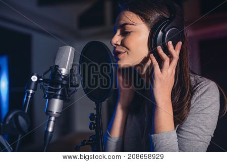 Female Vocal Artist Singing In A Recording Studio