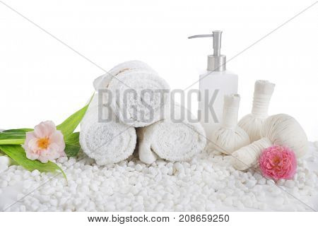 Rose,  on three rolled towel ,bottle oil with herbal ball.leaf on pile of white stones