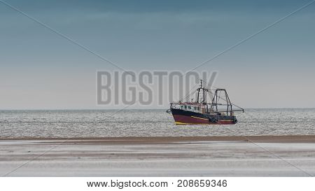 A small fishing trawler just off the seashore on the coast with its nets dropped in the water and very close to the shore