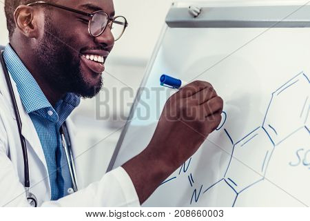 Up and coming professional. Scaled up look on an African American practitioner standing at a presentation board and drawing a chemical formula with a navy blue marker.