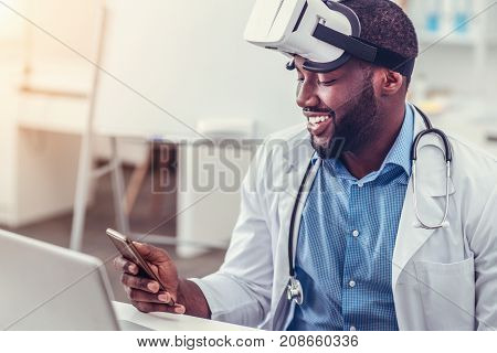 Innovative technologies. Side view on a beaming medical professional looking at a screen of his phone while sitting at a laptop and wearing a VR goggles at work.