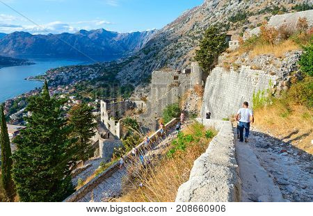 KOTOR MONTENEGRO - SEPTEMBER 8 2017: Unknown tourists descend on steps at ancient fortress walls over Kotor and Bay of Kotor Montenegro