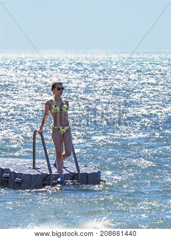 A Sweet Girl In A Swimsuit Descending From A Flexible Pier Into The Sea, Travel And Active Lifestyle