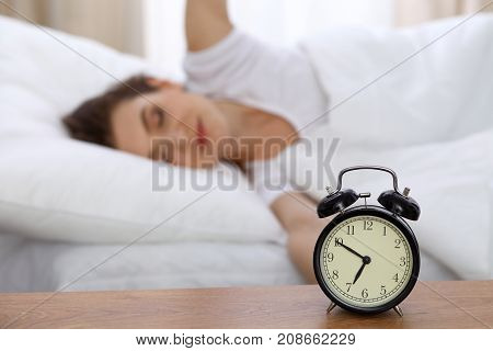 Beautiful sleeping woman resting in bed and trying to wake up with alarm clock.