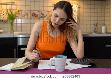 young long-haired woman student housewife with worried look handles most of the paperwork home budget Bank documents bills sitting at kitchen table with calculator and Notepad.