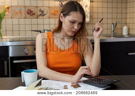 attractive young woman girl sitting at the kitchen table working with documents calculate home budget bills account statements using the calculator. Portrait in the kitchen in casual clothes.