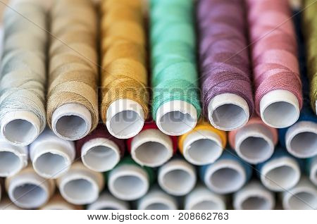 Close-up on colored sewing threads on spools