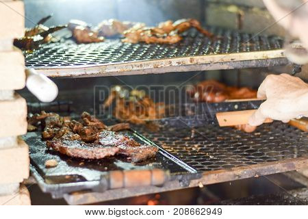 Brazilian Man Tending To Churrasco