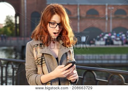 Surprised happy redhead woman in eyeglasses and autumn clothes read message on smartphone outdoors. surprised young woman of European appearance walking in the autumn Park reading a message on a smartphone