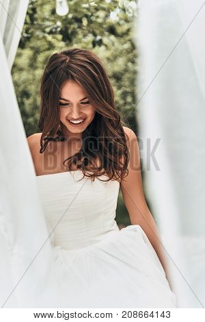 Happy bride. Attractive young woman in wedding dress looking down and smiling while standing outdoors