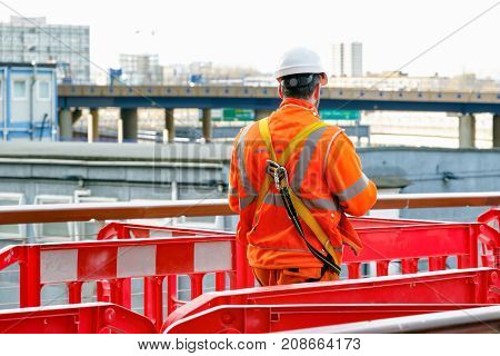 Back View Of A Construction Worker Walking Into A Building Site In Canary Wharf