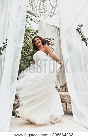 Dancing bride. Full length of attractive young woman in wedding dress smiling and looking at camera while spinning around outdoors