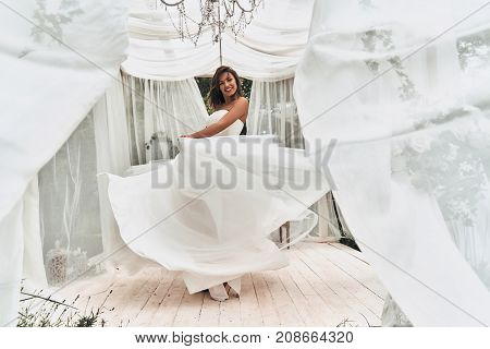 Happy to be married. Full length of attractive young woman in wedding dress smiling while dancing in the wedding pavilion outdoors